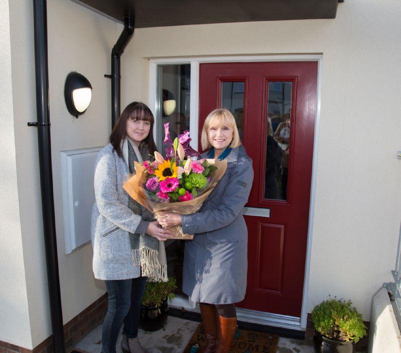 Kathy Mackenzie (THA Board of Management) presents flowers to Ms Brennan (THA tennant)